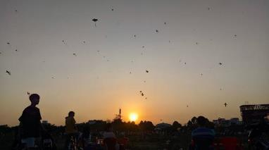 A group of people flying kites in the air  Description automatically generated